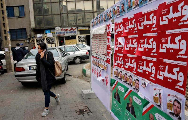 An Iranian woman walks past electoral posters in Tehran