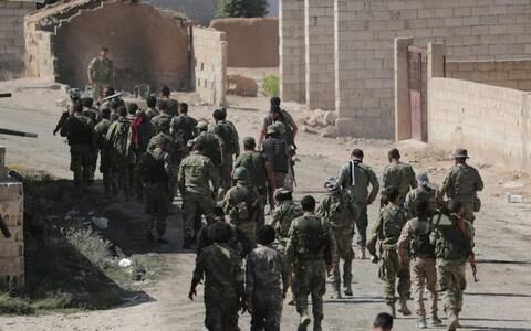 Turkey-backed Syrian rebel fighters walk together near the border town of Tel Abyad, Syri - Credit: REUTERS/Khalil Ashawi