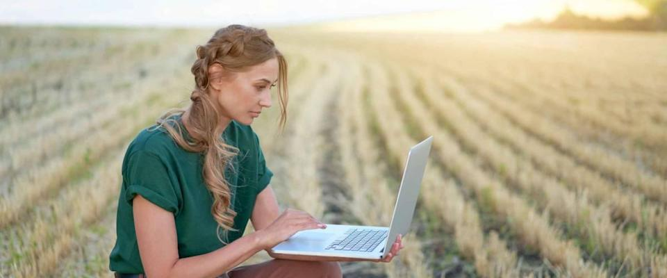 Woman farmer smart farming standing farmland smiling using laptop Female agronomist specialist research monitoring analysis data agribusiness Caucasian worker agricultural field