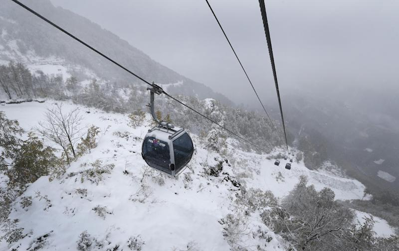 """Gondolas move as people make their way to the top of """"Rosa Khutor"""" Alpine center in Sochi, Russia, Wednesday, Sept. 25, 2013. The base of the center will host all alpine skiing competition during Olympics Games in February 2014. (AP Photo/Sergei Grits)"""