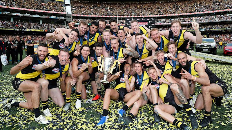 Richmond's squad are pictured here with the 2019 AFL premiership trophy.