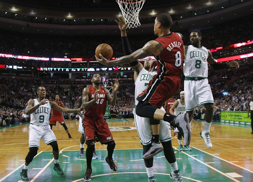 Miami Heat forward Michael Beasley (8) leaps behind the basket to make a play as Boston Celtics center Jared Sullinger (7) and forward Jeff Green (8) defend during the first quarter of an NBA basketball game in Boston on Wednesday, March 19, 2014. Watching are Celtics guard Rajon Rondo (9) and Heat forward Udonis Haslem (40).(AP Photo/Elise Amendola)
