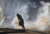 An anti-government protester runs from the smoke of tear gas, during clashes with riot police in Beirut, Lebanon, Saturday, Aug. 8, 2020. Dozens of Lebanese protesters stormed the buildings of a number of government ministries as well as the headquarters of the banking association. (AP Photo/Hussein Malla)