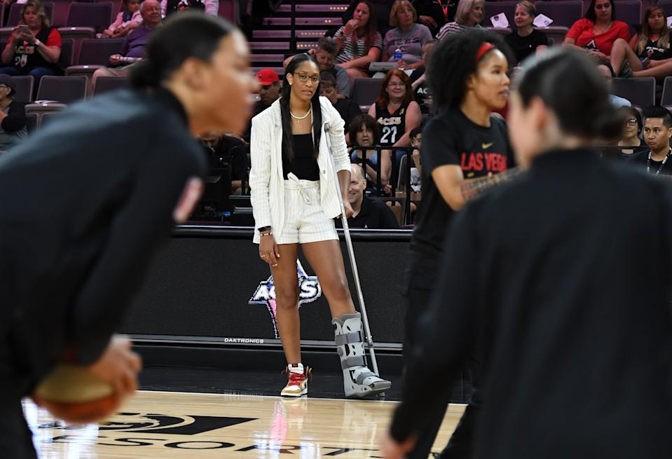 LAS VEGAS, NEVADA - JULY 21:  A'ja Wilson #22 of the Las Vegas Aces watches her teammates warm up before a game against the Minnesota Lynx at the Mandalay Bay Events Center on July 21, 2019 in Las Vegas, Nevada. Wilson suffered a sprained ankle in a game against Seattle on July 19. NOTE TO USER: User expressly acknowledges and agrees that, by downloading and or using this photograph, User is consenting to the terms and conditions of the Getty Images License Agreement.  (Photo by Ethan Miller/Getty Images)