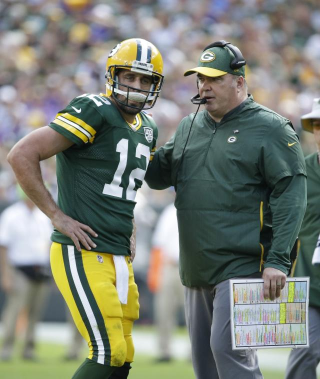 FILE - In this Sept. 16, 2018, file photo, Green Bay Packers coach Mike McCarthy talks to quarterback Aaron Rodgers during the second half of the team's NFL football game against the Minnesota Vikings in Green Bay, Wis. Following the Packers' 22-0 victory over Buffalo last week, Rodgers called the offense terrible and was critical of the plan spearheaded by McCarthy. On Wednesday, Oct. 3, Rodgers downplayed any rift with the man who has been his coach for his entire 13-year career. (AP Photo/Mike Roemer, File)