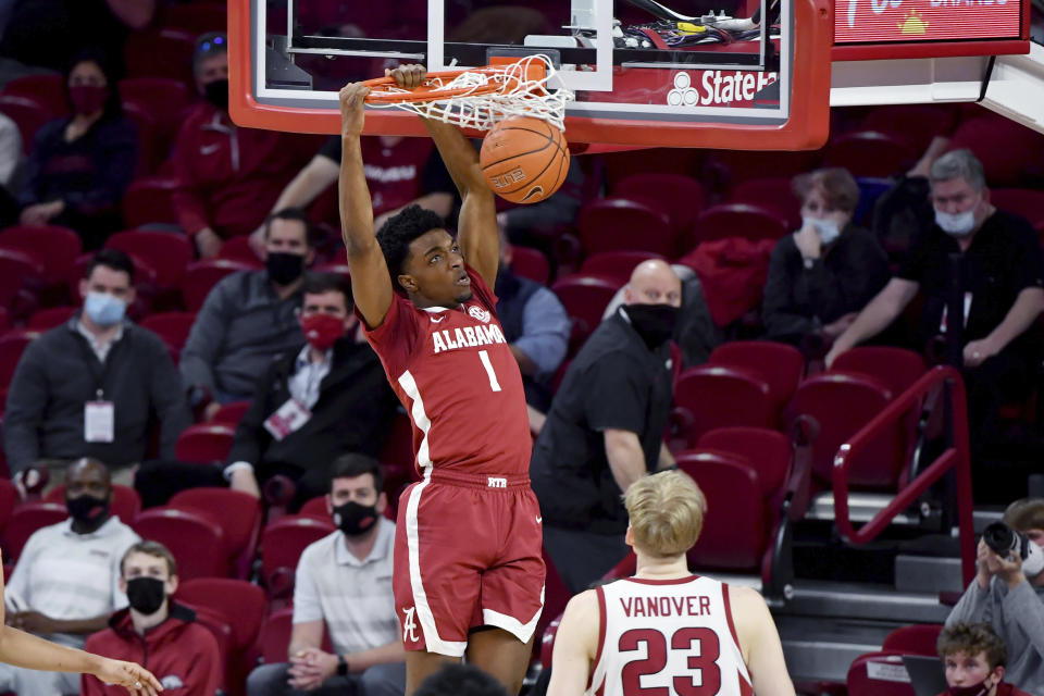 FILE - Alabama forward Herbert Jones (1) dunks the ball over Arkansas forward Connor Vanover (23) during the first half of an NCAA college basketball game in Fayetteville, Ark., in this Wednesday, Feb. 24, 2021, file photo. Alabama senior Herbert Jones is The Associated Press Player of the Year in the Southeastern Conference and a member of the All-SEC team in voting announced Tuesday, March 9, 2021. (AP Photo/Michael Woods, File)