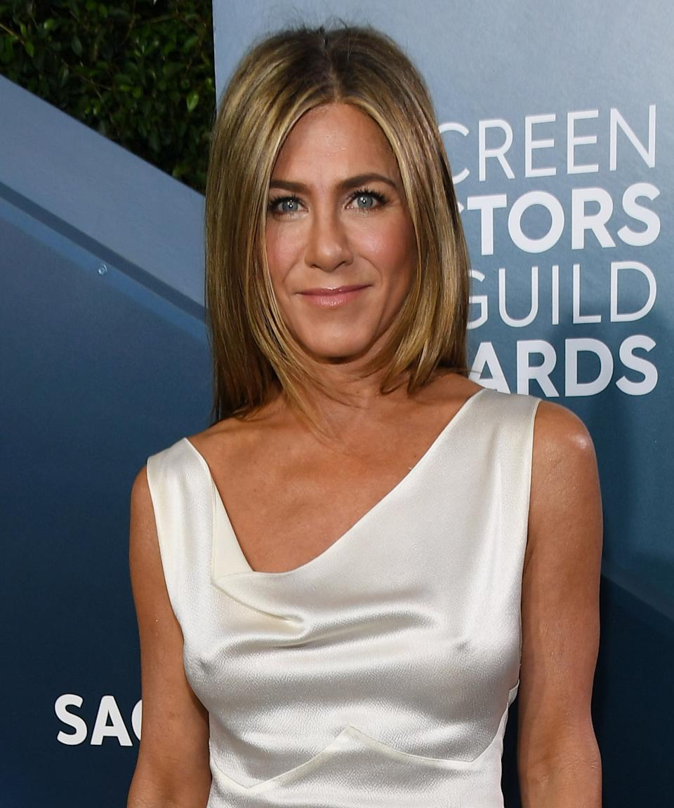 """<h3>2020: Soft & Pulled Back</h3><br>In Aniston's most recent appearance at the SAG Awards in January, she paired her <a href=""""https://www.refinery29.com/en-us/2020/01/9240149/jennifer-aniston-sag-awards-white-dress-vintage-dior"""" rel=""""nofollow noopener"""" target=""""_blank"""" data-ylk=""""slk:vintage Dior white silk gown"""" class=""""link rapid-noclick-resp"""">vintage Dior white silk gown</a> with pared-down glam: <a href=""""https://www.refinery29.com/en-us/2019/12/8995352/makeup-trends-2020"""" rel=""""nofollow noopener"""" target=""""_blank"""" data-ylk=""""slk:barely-there makeup"""" class=""""link rapid-noclick-resp"""">barely-there makeup</a> and hair down, tucked back behind her shoulders.<span class=""""copyright"""">Photo: Kevin Mazur/Getty Images.</span>"""