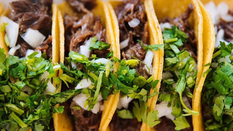 a photo of several beef tacos in a line