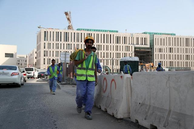 Migrant workers are seen walking next to a construction site in the Qatari capital Doha on December 6, 2016 (AFP Photo/STRINGER)