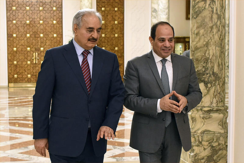 FILE - In this May 9, 2019 file photo, provided by Egypt's presidency media office, Egyptian President Abdel-Fattah el-Sissi, right, walks with military commander Khalifa Hifter, the head of the self-styled Libyan National Army, in Cairo, Egypt. The Egyptian Parliament is likely to vote Monday, July 20, 2020, to authorize the country's president to deploy troops to war-torn Libya if Turkey-backed forces allied with the U.N.-supported government in Tripoli move to retake the strategic coastal city of Sirte. The country is now split between a government in the east, allied with Hifter, and one in Tripoli, in the west, supported by the United Nations. Along with Egypt, Hifter is also backed by the United Arab Emirates and Russia, while the in addition to Turkey, the Tripoli forces are aided by Qatar and Italy. (Egyptian Presidency Media office via AP, File)