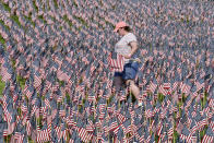 A volunteer walks through a field of American flags planted on Boston Common ahead of Memorial Day, Wednesday, May 26, 2021, in Boston. After more than a year of isolation, American veterans are embracing plans for a more traditional Memorial Day. They say wreath-laying ceremonies, barbecues at local vets halls and other familiar events are a welcome chance to reconnect with fellow service members and renew solemn traditions honoring the nation's war dead. (AP Photo/Josh Reynolds)