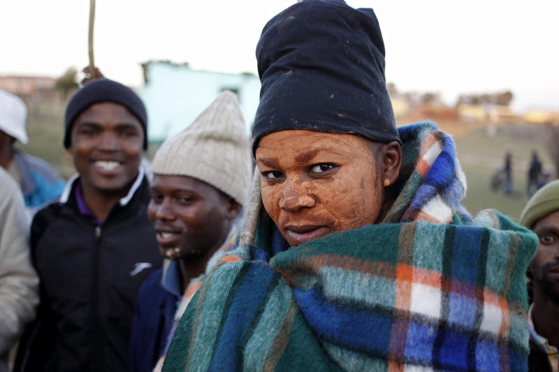 In this photo taken on Thursday, July 11, 2013, men dance around a boy, covered with a blanket, after he completed his initiation ceremony near Qunu, South Africa. Initiation ceremonies in South Africa's Eastern Cape province have led to the deaths of more than 60 young men since May and the hospitalization of hundreds, sparking concern from government and health officials about the lack of regulation of a national tradition that determines when a boy becomes a man. (AP Photo/Schalk van Zuydam)