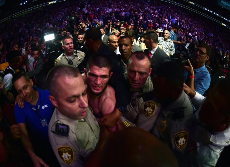 Security escorts Khabib Nurmagomedov out of T-Mobile arena amid the chaos that followed his UFC 229 victory over Conor McGregor