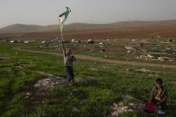 Bedouin boys play with Palestinian flags after Israeli troops demolished tents and other structures of the Khirbet Humsah hamlet in the Jordan Valley in the West Bank, Wednesday, Feb. 3, 2021. A battle of wills is underway in the occupied West Bank, where Israel has demolished the herding community of Khirbet Humsu three times in as many months, displacing dozens of Palestinians. Each time they have returned and tried to rebuild, saying they have nowhere else to go. (AP Photo/Maya Alleruzzo)