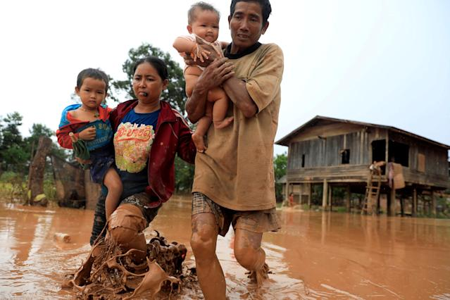 <p>Parents carry their children as they leave their home during the flood after the Xepian-Xe Nam Noy hydropower dam collapsed in Attapeu province, Laos, July 26, 2018. (Photo: Soe Zeya Tun/Reuters) </p>