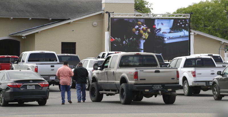 Due to the COVID-19 outbreak, funeral services, like the one depicted at Mission Park Funeral Chapels, are shown on an outdoor screen to drive-up attendees. (AP Photo/Eric Gay)