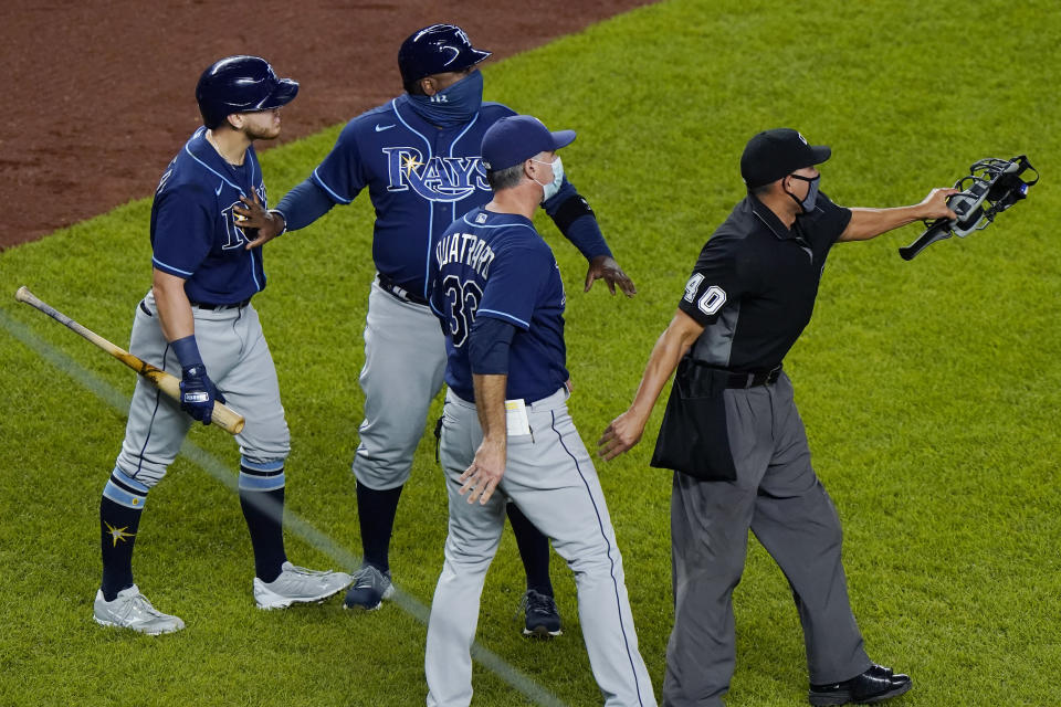 """FILE - In this Sept. 1, 2020, file photo, Tampa Bay Rays pinch-hitter Michael Brosseau, left, is restrained by a coach as second base umpire Chad Fairchild (4) warns New York Yankees relief pitcher Aroldis Chapman to stay away from Brosseau as the two players exchanged words following the Rays' 5-3 loss to the Yankees in a baseball game at Yankee Stadium in New York. The altercation started after Chapman threw a high pitch at Brosseau. The Rays wear blue T-shirts with four horses lined up behind a fence, a reference to Tampa Bay manager Kevin Cash declaring """"I've got a whole damn stable full of guys that throw 98 miles an hour"""" in response to Aroldis Chapman throwing near the Mike Brosseau's head on Sept. 1. (AP Photo/Kathy Willens, File)"""