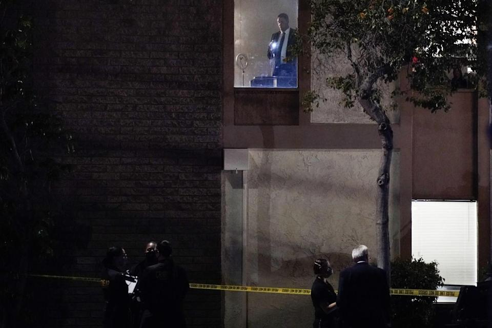 Police stand outside yellow crime scene tape around a building as a man with a flashlight is seen in a second-story window