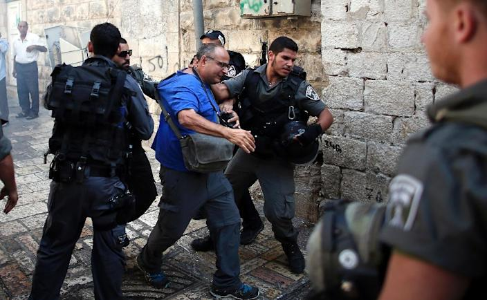 AFP Israeli photographer Menahem Kahana (C) is roughed up by an Israeli policeman during a demonstration in a street in the Muslim quarter of Jerusalem's Old City, on October 4, 2015 (AFP Photo/Thomas Coex)
