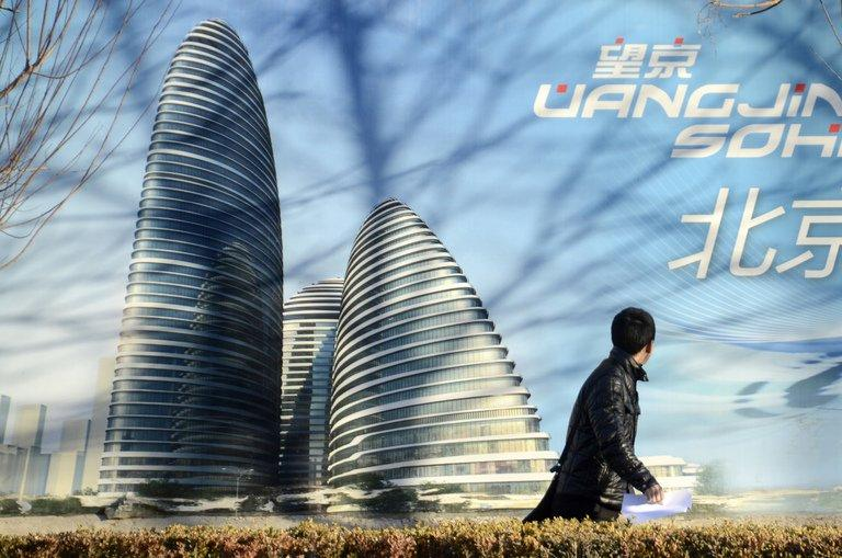 A man walks past a billboard of the Wang Jing SOHO complex by architect Zaha Hadid in Beijing, January 3, 2013