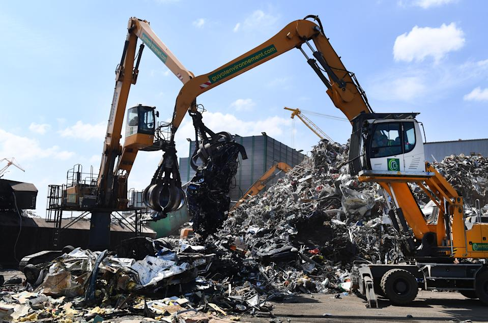This picture taken on July 2, 2019 in Guyot Environnement recycling company shows cranes lifting an old scrap car next to a pile of mettalic waste, in Brest, western France. - Guyot Environnement announced on July 2, 2019 the buy-out of the Spanish company Hirumet. (Photo by Fred TANNEAU / AFP)        (Photo credit should read FRED TANNEAU/AFP/Getty Images)