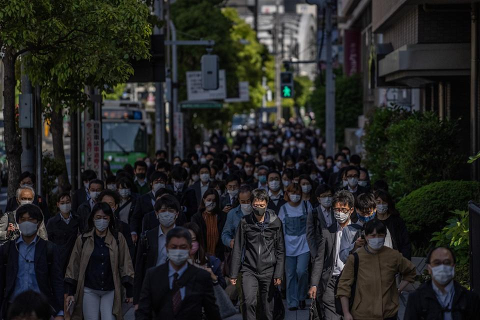 People wearing face masks walk to work on April 23, 2021 in Tokyo, Japan.