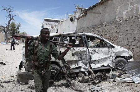 Somali government soldiers walks next to car damaged from explosion near Al Mukaram hotel in Mogadishu