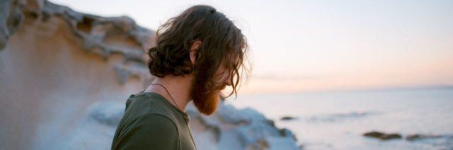 man on a beach with long hair looking down