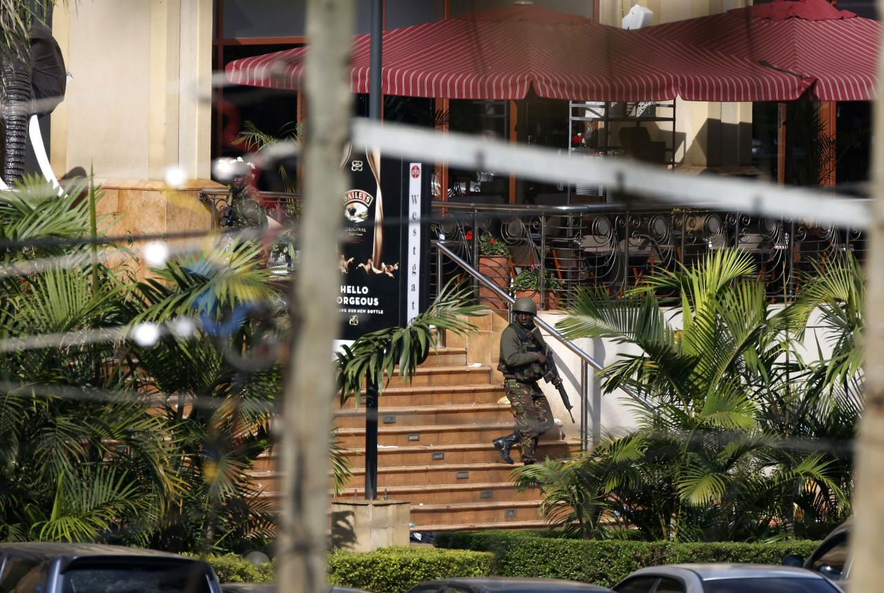 A Kenyan soldier walks out of the main gate of Westgate Shopping Centre in Nairobi September 22, 2013. Islamist militants were holed up with hostages on Sunday at the shopping mall in Nairobi, where at least 59 people have been killed in an attack by the al Shabaab group that opposes Kenya's participation in a peacekeeping mission in neighbouring Somalia. A volley of gunfire lasting about 30 seconds interrupted a stalemate of several hours, a Reuters witness said, speaking from near the Westgate shopping centre that has several Israeli-owned outlets and is frequented by expatriates and Kenyans. REUTERS/Goran Tomasevic (KENYA - Tags: CIVIL UNREST MILITARY)