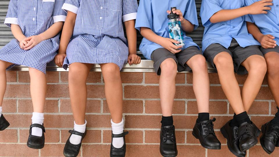 Low section view of five school children sitting on brick wall wearing school uniform. Children's legs and feet in black shoes hanging down