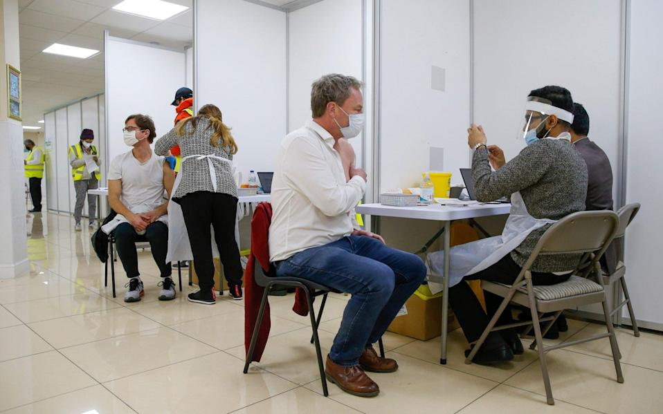 Visitors receive a dose of the Covid vaccine - Hollie Adams/Bloomberg