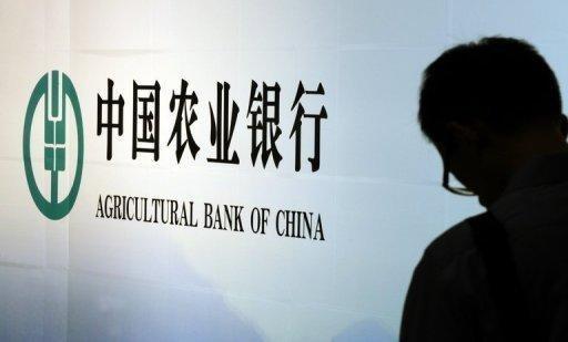 People walk past advertising for Agricultural Bank of China