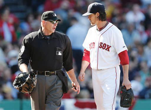 Boston Red Sox starting pitcher Clay Buchholz talks with home plate Ed Hickox after the fourth inning of a baseball game against the Baltimore Orioles at Fenway Park in Boston Monday, April 8, 2013. (AP Photo/Winslow Townson)
