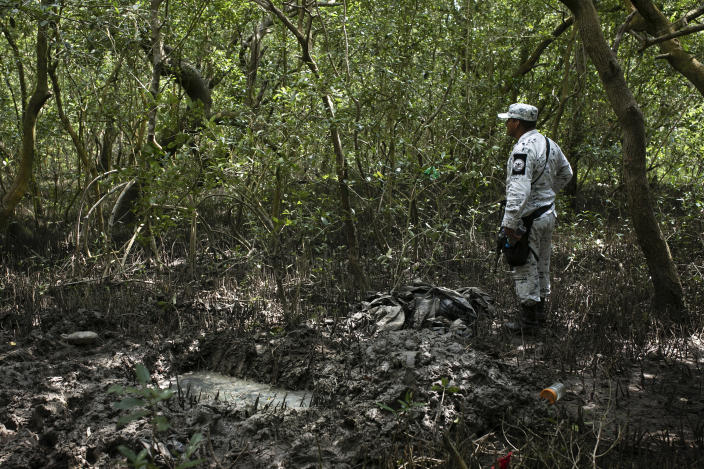 A member of the National Guard stands next to a clandestine grave in Puquita, a tropical mangrove island near Alvarado in the Gulf coast state of Veracruz, Mexico, Thursday, Feb. 18, 2021. Investigators from the National Search Commission found three pits with human remains and plastic bags inside. The number of bodies there has not yet been determined. (AP Photo/Felix Marquez)
