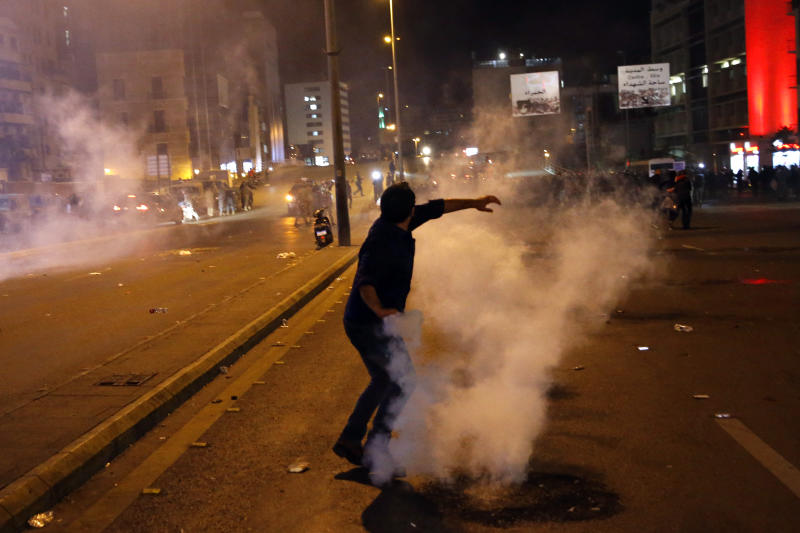 A protester throws back tear gas canister that was fired towards them by Lebanese riot police during an anti-government protest in Beirut, Lebanon, Wednesday, Dec. 4, 2019. Protesters have been holding demonstrations since Oct. 17 demanding an end to corruption and mismanagement by the political elite that has ruled the country for three decades. (AP Photo/Bilal Hussein)