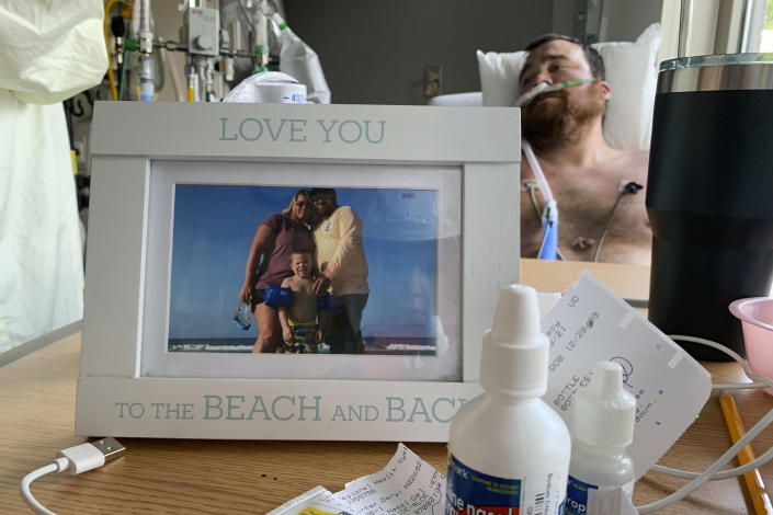 A framed photo of his family sits in front of Daryl Barker as he slowly recovers from COVID-19 inside Lake Regional Hospital's ICU in Osage Beach, Mo., on Monday, July 26, 20021. Barker had chosen not to be vaccinated against the virus but his long hospitalization has forced him to reconsider. (AP Photo/Sarah Blake Morgan)