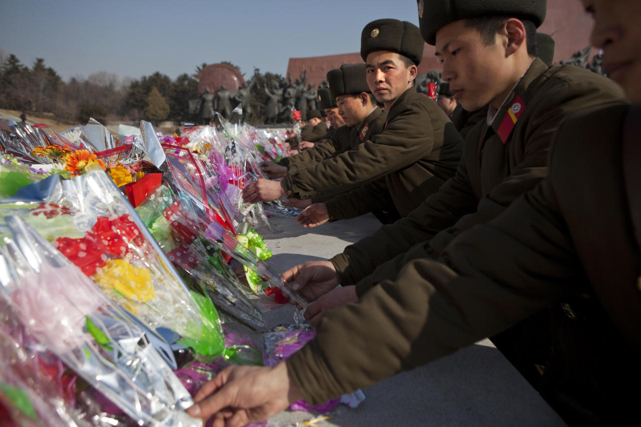 North Korean soldiers lay flowers at the base of bronze statues of the late leaders Kim Il Sung and Kim Jong Il to pay their respects in Pyongyang, North Korea on Saturday, Feb. 16, 2013. North Koreans turned out to commemorate what would have been the 71th birthday of Kim Jong Il who died on Dec. 17, 2011. (AP Photo/David Guttenfelder)