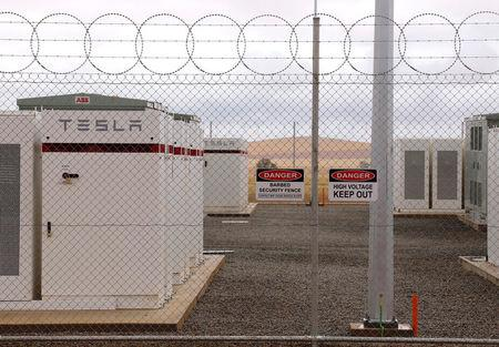Warning signs adorn the fence surrounding the compound housing the Hornsdale Power Reserve featuring the world's largest lithium ion battery made by Tesla during the official launch near the South Australian town of Jamestown