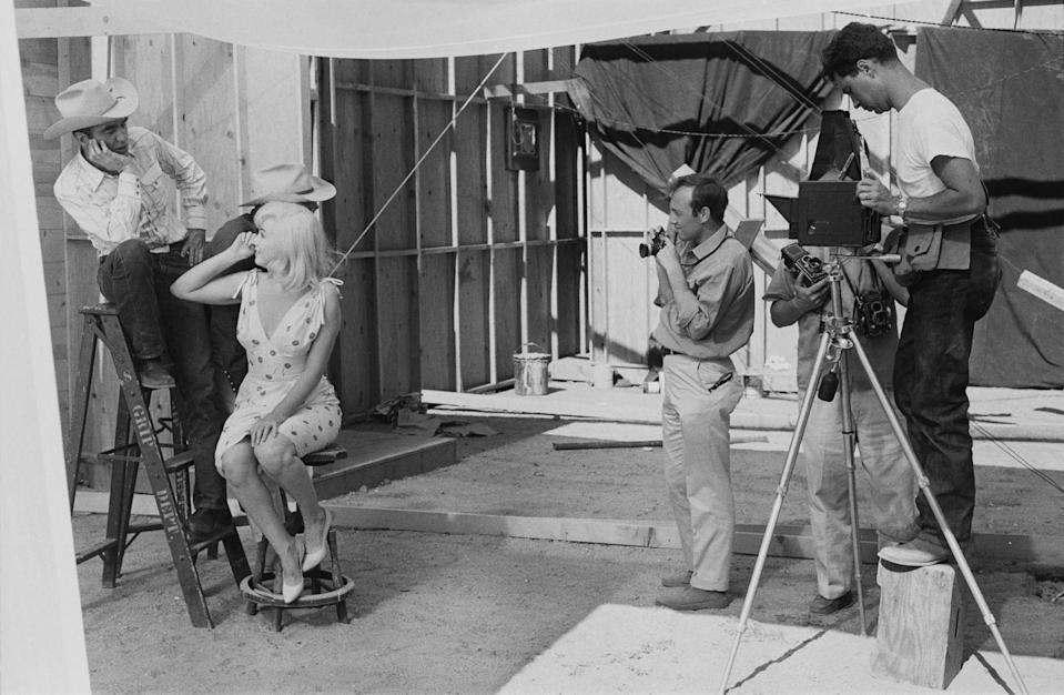 """<p>Film photographers set up a shot for Marilyn and her co-stars Clark Gable and Montgomery Clift during the shooting of <a href=""""https://www.amazon.com/Misfits-Clark-Gable/dp/B00FJVBSP6/ref=sr_1_3?keywords=the+misfits&qid=1562959687&s=gateway&sr=8-3&tag=syn-yahoo-20&ascsubtag=%5Bartid%7C10050.g.28612852%5Bsrc%7Cyahoo-us"""" rel=""""nofollow noopener"""" target=""""_blank"""" data-ylk=""""slk:The Misfits"""" class=""""link rapid-noclick-resp""""><em>The Misfits</em></a>. The screenplay was written by her husband, Arthur Miller. It was Marilyn's last completed film. </p>"""