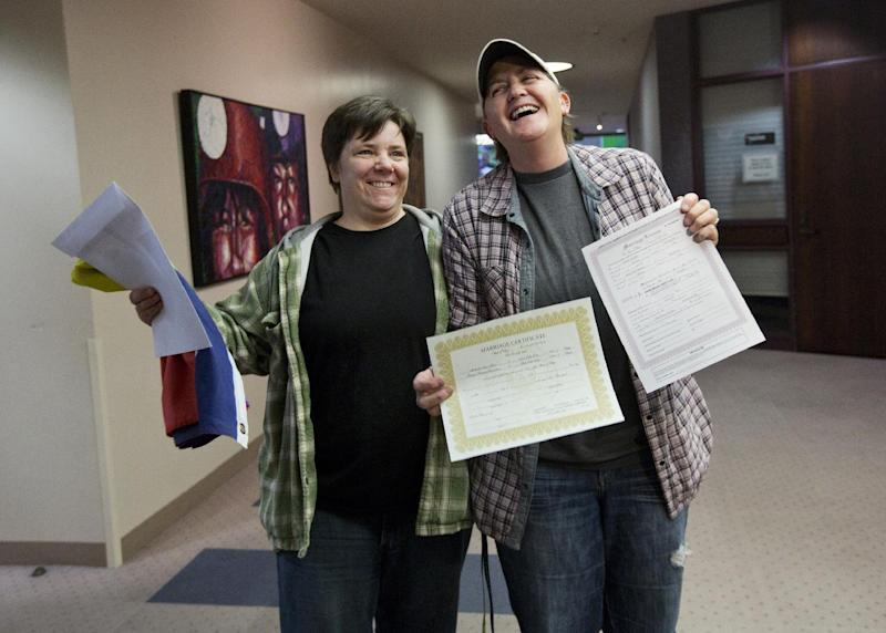 "FILE -- In this Dec. 20, 2013 file photo, Elise Larsen, left, and Samantha Christensen, right, show off their marriage license after being one of the first same sex couples to receive one at the Salt Lake County Clerk's Office in Salt Lake City, Utah. Since the U.S. Supreme Court threw out provisions of the Defense of Marriage Act, which had defined marriage as a ""legal union between one man and one woman,"" gay couples ""will be treated as married for all federal tax purposes ...,"" the IRS says. (AP Photo/Kim Raff, File)"