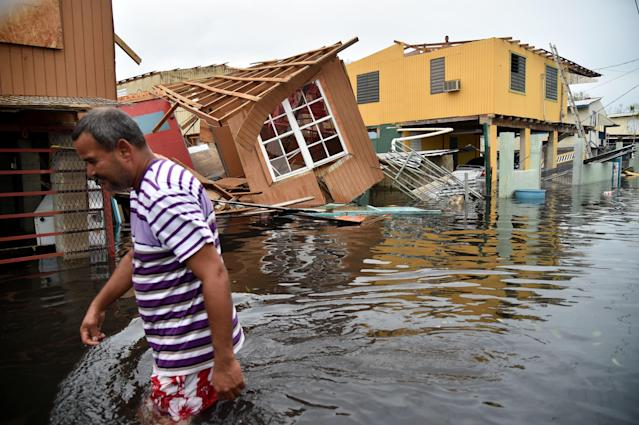 A man walks past a house lying in floodwater in Catano town in Juana Matos, Puerto Rico, on Sept. 21, 2017. (HECTOR RETAMAL via Getty Images)