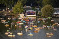The Staatsphilharmonie plays a concert on the lake stage on the Gro'er Dutzendteich in front of spectators who watch the concert on their own boats, Saturday, Aug. 1, 2020, in Nuremberg, Germany. Due to the musical events Bardentreffen, Klassik Open Air and Stars in Luitpoldhain, which were cancelled due to the coronavirus, the project office in the Culture Division of the City of Nuremberg has organized three different concerts with an open-air concert weekend on the banks of the Dutzendteich. (Daniel Karmann/dpa via AP)