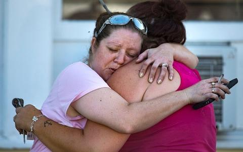 Carrie Matula embraces a woman after a fatal shooting at the First Baptist Church in Sutherland Springs - Credit: Nick Wagner/Austin American-Statesman via AP