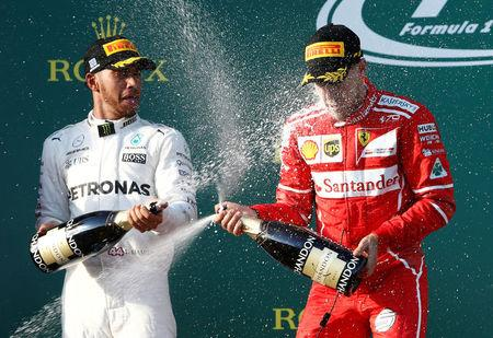 Formula One - F1 - Australian Grand Prix - Melbourne, Australia - 26/03/2017 - Ferrari driver Sebastian Vettel of Germany (R) sprays champagne alongside second-placed Mercedes driver Lewis Hamilton of Britain on the podium. REUTERS/Brandon Malone     TPX IMAGES OF THE DAY