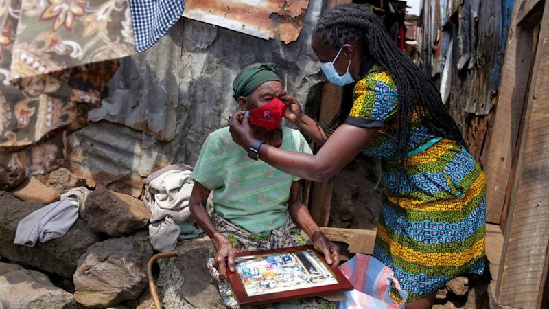 A woman member of a local organization is seen donating a facemask to an elderly lady in Mathare Slums amid the coronavirus pandemic.