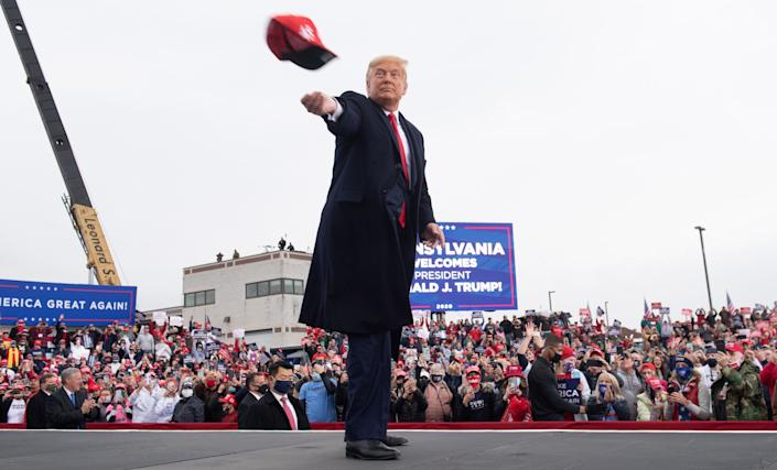 President Donald Trump throws a MAGA hat into the crowd as he arrives for a Make America Great Again campaign rally at Altoona-Blair County Airport in Martinsburg, Pa., on Oct. 26.