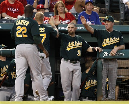 Oakland Athletics' Chris Carter (22) and Brandon Moss are congratulated by Brandon Moss (37) and manager Bob Melvin, right, in the dugout after the two scored on Josh Donaldson's single in the first inning of a baseball game against the Texas Rangers, Wednesday, Sept. 26, 2012, in Arlington, Texas. (AP Photo/Tony Gutierrez)