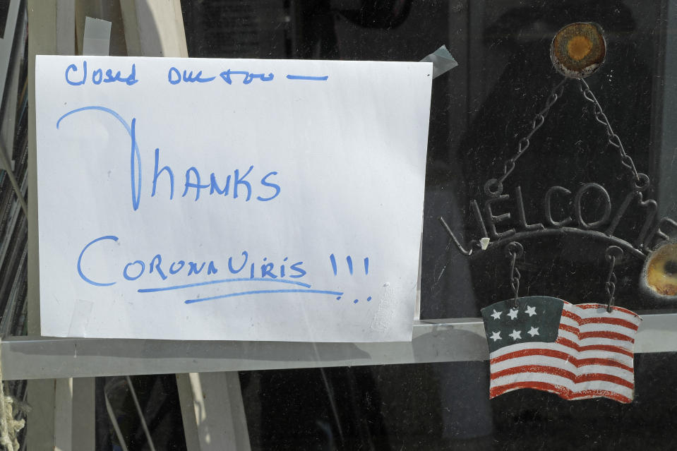 In this May 21, 2020 photo, a sign on a business in Tenino, Wash., says they are closed due to the coronavirus and state stay-at-home restrictions. In an effort to help residents and local merchants alike get through the economic fallout of the coronavirus pandemic, the small town has issued wooden currency for residents to spend at local businesses, decades after it created a similar program during the Great Depression. (AP Photo/Ted S. Warren)