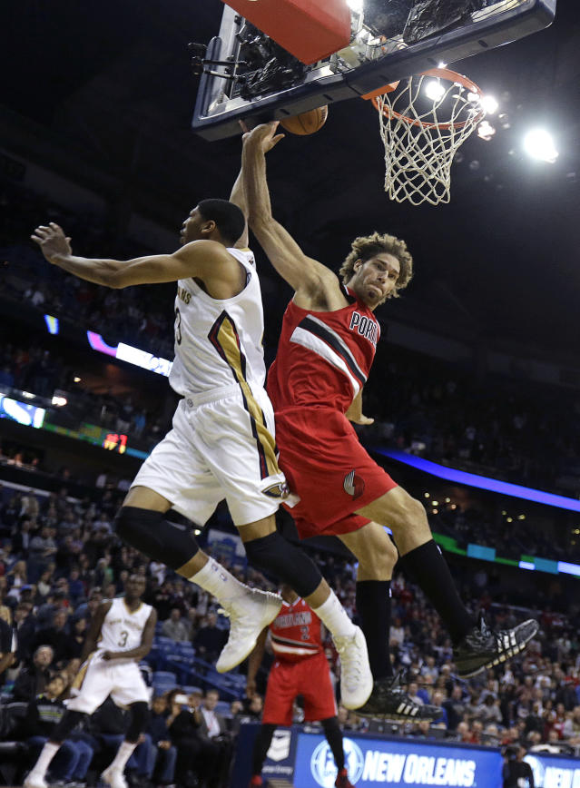 New Orleans Pelicans forward Anthony Davis goes to the basket against Portland Trail Blazers center Robin Lopez, right, in the first half of an NBA basketball game in New Orleans, Monday, Dec. 30, 2013. (AP Photo/Gerald Herbert)