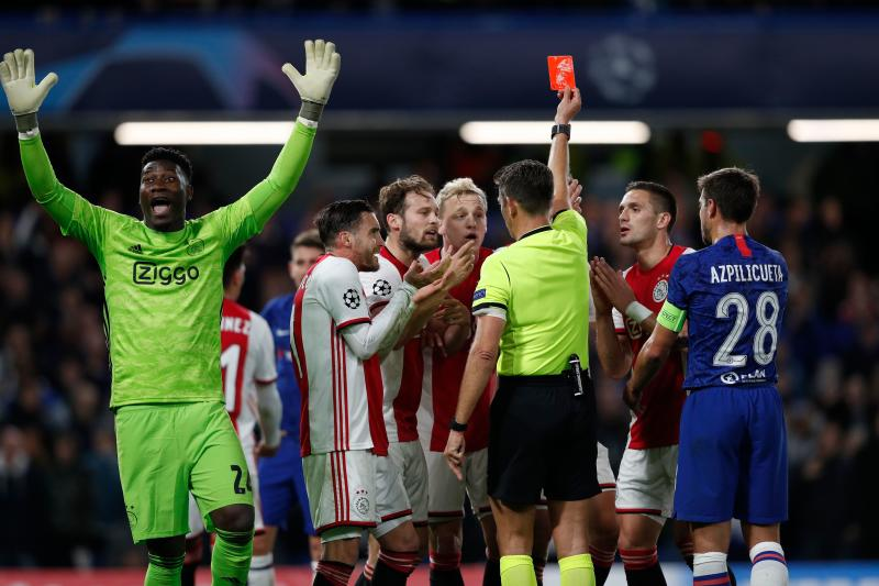 Ajax's players react after Ajax's Dutch defender Joel Veltman (hidden) is shown a red card by Italian referee Gianluca Rocchi during the UEFA Champion's League Group H football match between Chelsea and Ajax at Stamford Bridge in London on November 5, 2019. - The game finished 4-4. (Photo by Adrian DENNIS / AFP) (Photo by ADRIAN DENNIS/AFP via Getty Images)